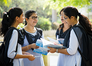 Girl students talking together about their studies project at university campus in India – CRS Photo - Shutterstock